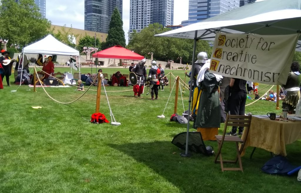People in costume on a grassy field surrounded by rain shelters.